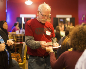 A volunteer receives an UltraShort from a woman with curly red hair. He is a white man in his 60s, wearing a red Ex Fabula tshirt and has glasses and a mustache.
