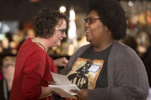 an Ex Fabula volunteer passes along surveys to guests at a StorySlam