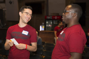 two young men have a conversation while volunteering at a StorySlam