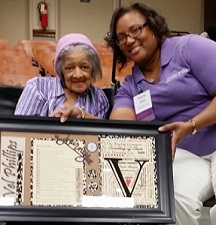 Vel Phillips stands next to a woman who holds up the framed artwork that was presented to Vel Phillips.