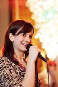Smiling women with dark hair speaking into a microphone