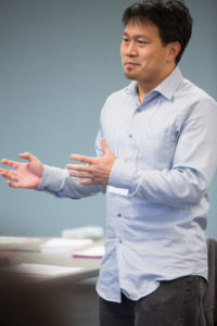 A Chinese man gesturing with open hands