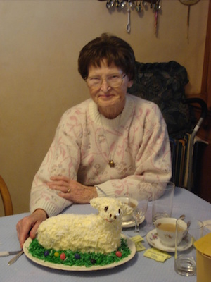 Woman with glasses, wearing a white and pink sweater, sitting behind a cake shaped like a lamb