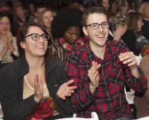 Smiling audience members applaud for the storytellers.
