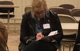 A college-age woman writes intently on a worksheet.