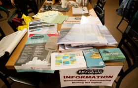A table with fliers and advertisments on it.
