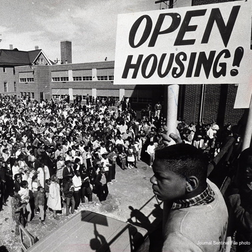 """Large group of Civil Rights Demonstrators; featuring a young Black man holding a sign that says """"Open Housing!"""""""