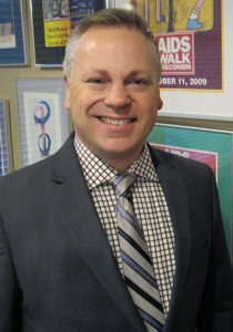 A smiling white man with short gray hair, wearing a suit, in front of some AIDS walk posters