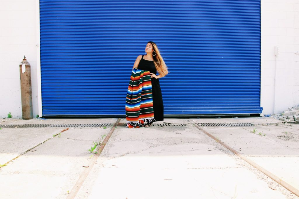 woman with long hair standing in front of a bright blue wall holding a Mexican blanket