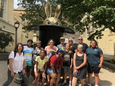 Group of all ages people attending Sculptures & Stories tours standing in front of outdoor sculpture.