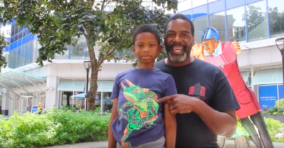 One older Black male wearing a blue tee shirt and his young son wearing a blue tee shirt with a lizard, standing in front of a sculpture talking about Sculptures and Stories.