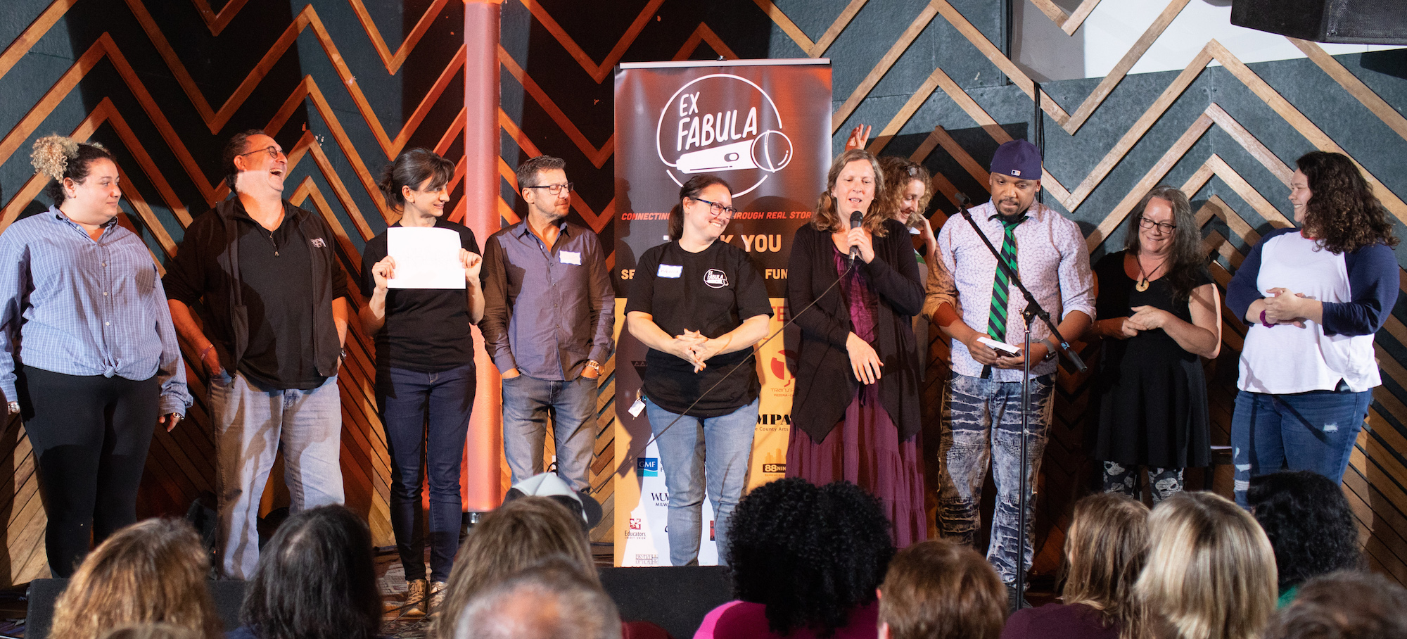 9 Adults standing in a line on stage reviewing their stories