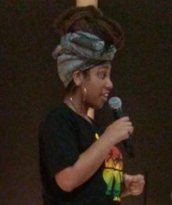 A young Black woman with hoop earrings, a head wrap, and a black Bob Marley t-shirt holds a microophone.